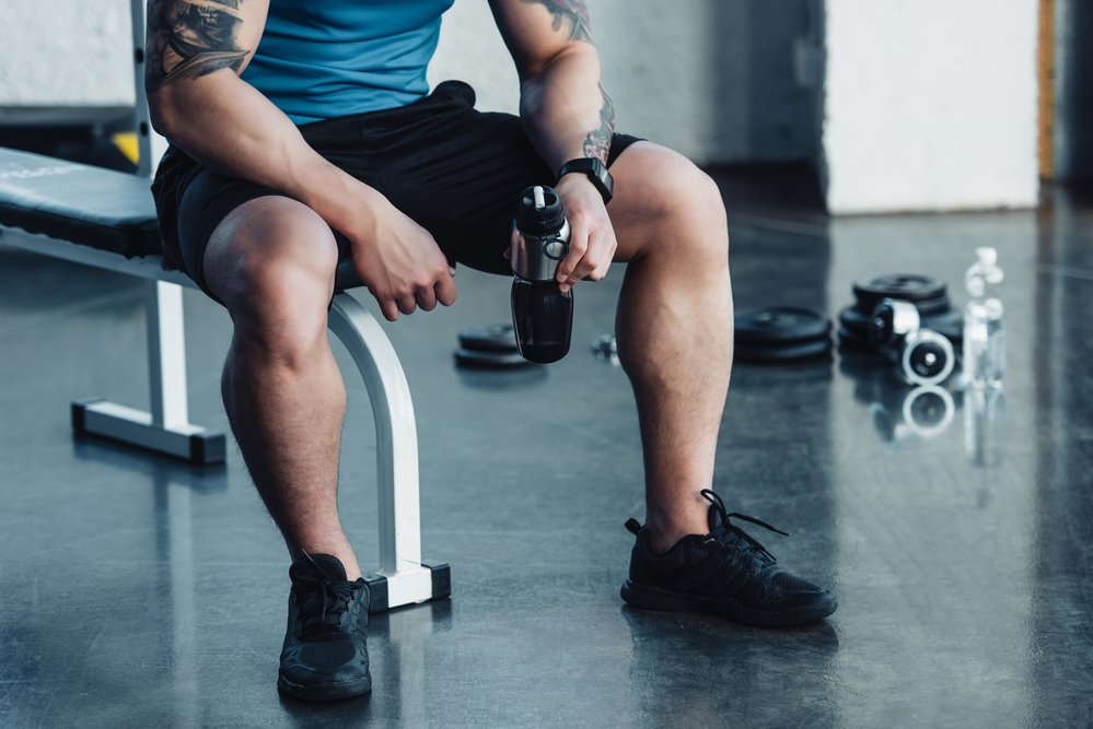 Cropped lower half of a muscular man, sitting on a weight bench, holding a blended protein powder shake.