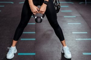 A fit woman doing CrossFit with a kettle bell. She'd be interested in the best protein shaker.