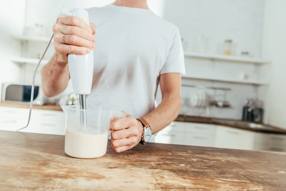 A man mixing a protein powder shake using a hand blender on a wooden kitchen bench