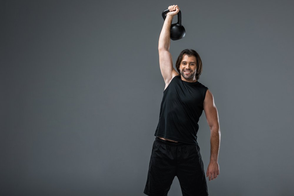 A muscular man, smiling at the camera and holding up a kettlebell as part of a crossfit training exercise
