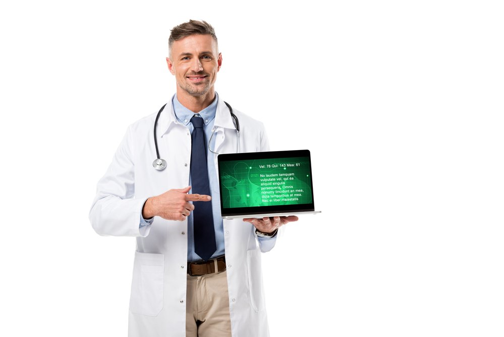 A male doctor holding a computer showing data. A health check may be important to avoid injury going into a new exercise routine.