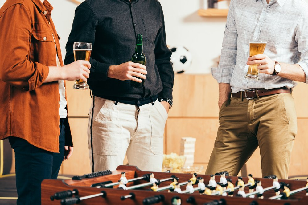 3 men standing and holding bears. Eating healthy snacks before drinking alcohol helps with burning calories by stopping impulse eating