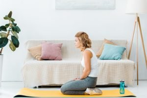 A tired young woman, kneeling on a yoga mat. Make no excuses and embrace exercise and a healthy diet.