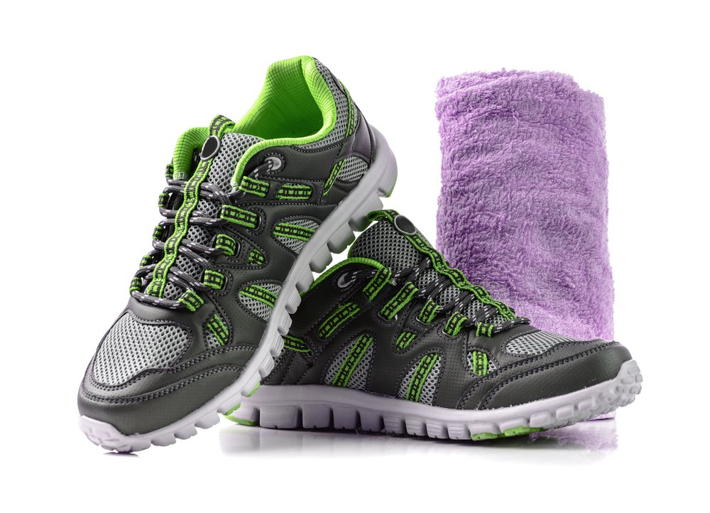 running shoes and a purple towel on a white background