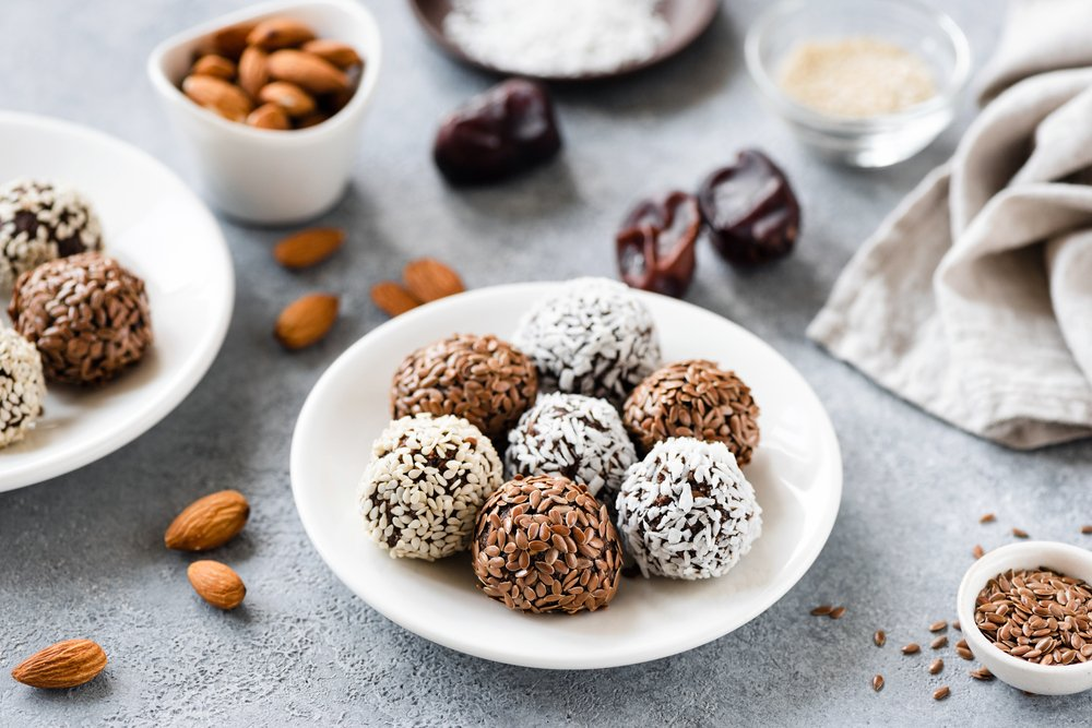 Bliss balls in the form of vegan protein energy balls in a white bowl, with ingredients scattered around.