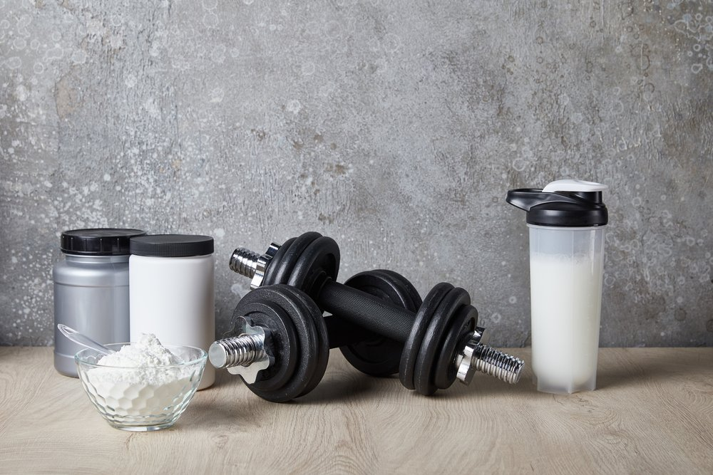 A protein shaker, some dumbbells and some protein powder - in canisters and loose in a bowl, all on a wooden top next to a concrete wall.