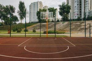 A basketball court near some high-rise housing blocks. City kids vs country kids and fitness.
