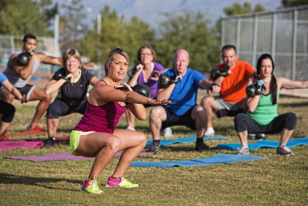 Mixed group of people doing a bootcamp exercise class