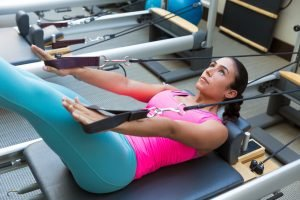 Pilates reformer workout exercises woman brunette at gym indoor. What is pilates?