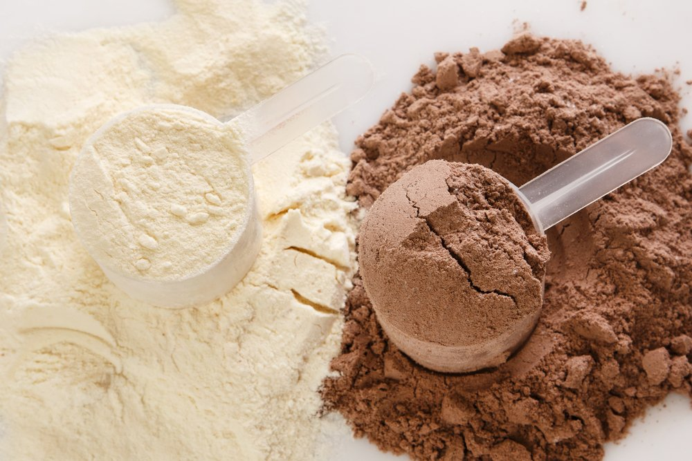 A close up of 2 scoops of protein powder. One vanilla protein powder and the other chocolate protein powder. Ready to be mixed in the best protein shaker. Products like this are being taken as part of the dry scooping craze.