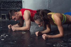 A fit man and woman doing plank exercises for core strength