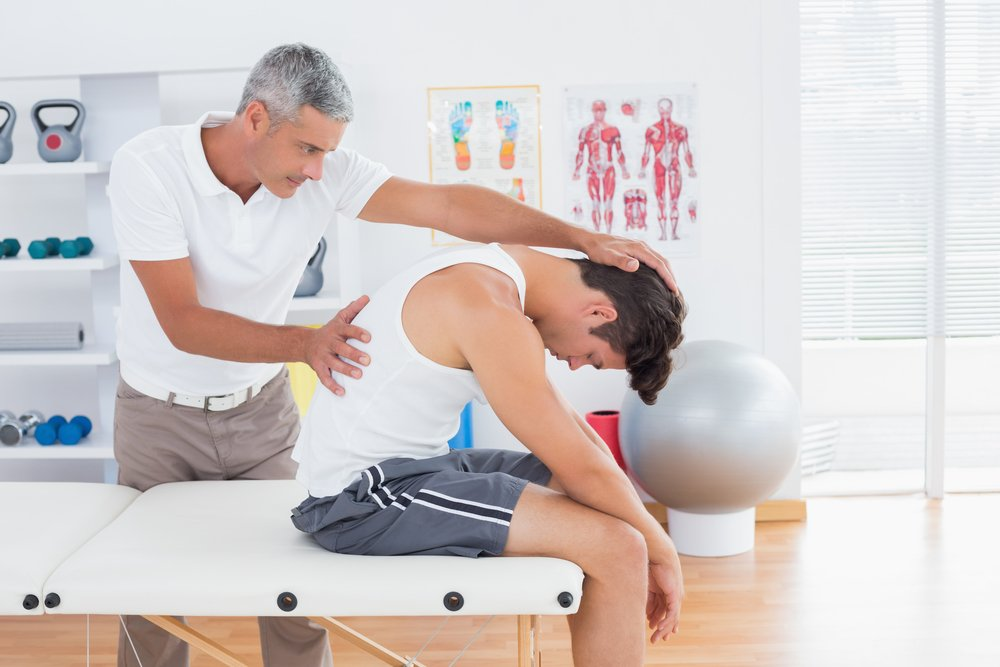 A chiropractor stretching a young man's back as part of a chiropractic treatment.