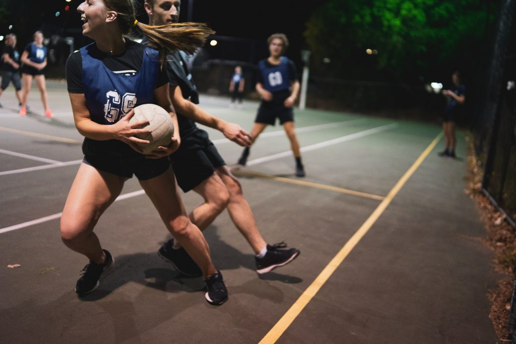 young girls playing netball under floodlights. It's important to get fit for netball before you play.