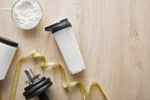 Protein powder in a bowl, a measuring tape, a dumbbell and the best protein shaker.
