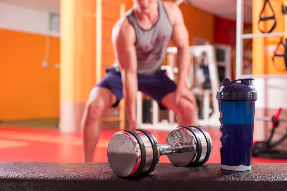 Whey protein shaker and dumbbells. Fitness and bodybuilding man in background doing exercise. Cleaning your new protein shaker can be a problem.