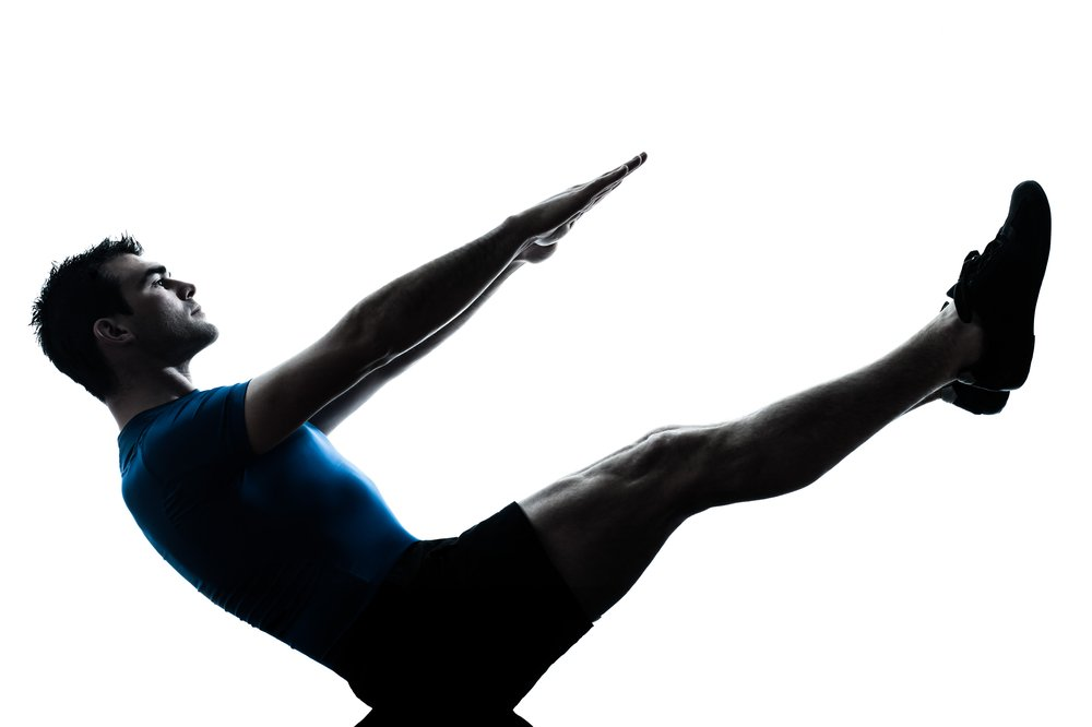 Pilates for men. one caucasian man exercising workout fitness boat position yoga in silhouette studio isolated on white background