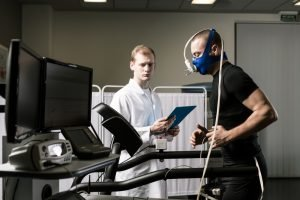 Shot of a male patient running on a treadmill with oxygen mask and doctor in white uniform. The man is performing a VO2 Test.