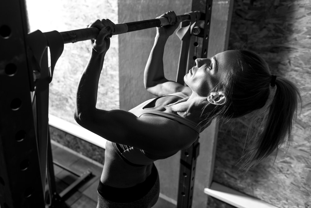 Doing chin ups. Slim well built young woman wearing a ponytail and holding a horizontal bar while doing chin ups