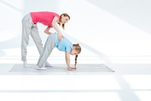 A woman helping a child to do a yoga pose. An example of yoga for kids