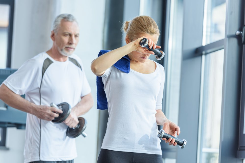tips for personal trainers include how to motivate clients. This photo shows a woman working out in the gym with her male personal trainer.