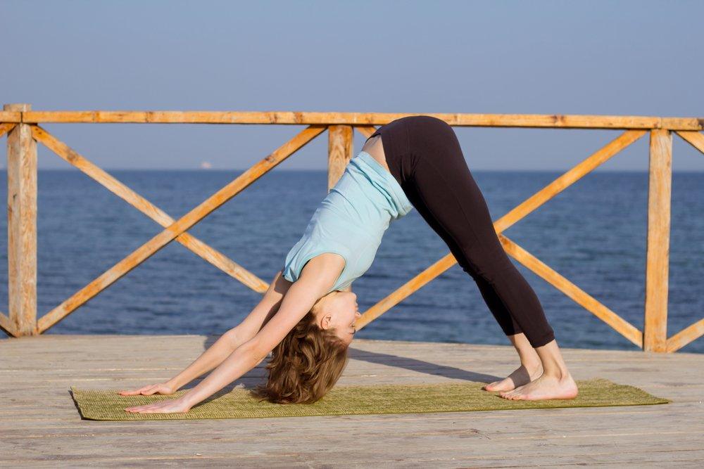 A young woman practising the dowward facing dog posture in yoga