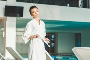 A young woman in a white bathroom on the edge of a spa/pool. Book a lifestyle retreat and re-invigorate yourself.