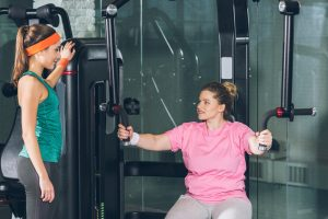 An unfit young woman wearing a pink top, sitting on an exercise machine with her personal trainer standing by. PTs have heard all the fitness excuses