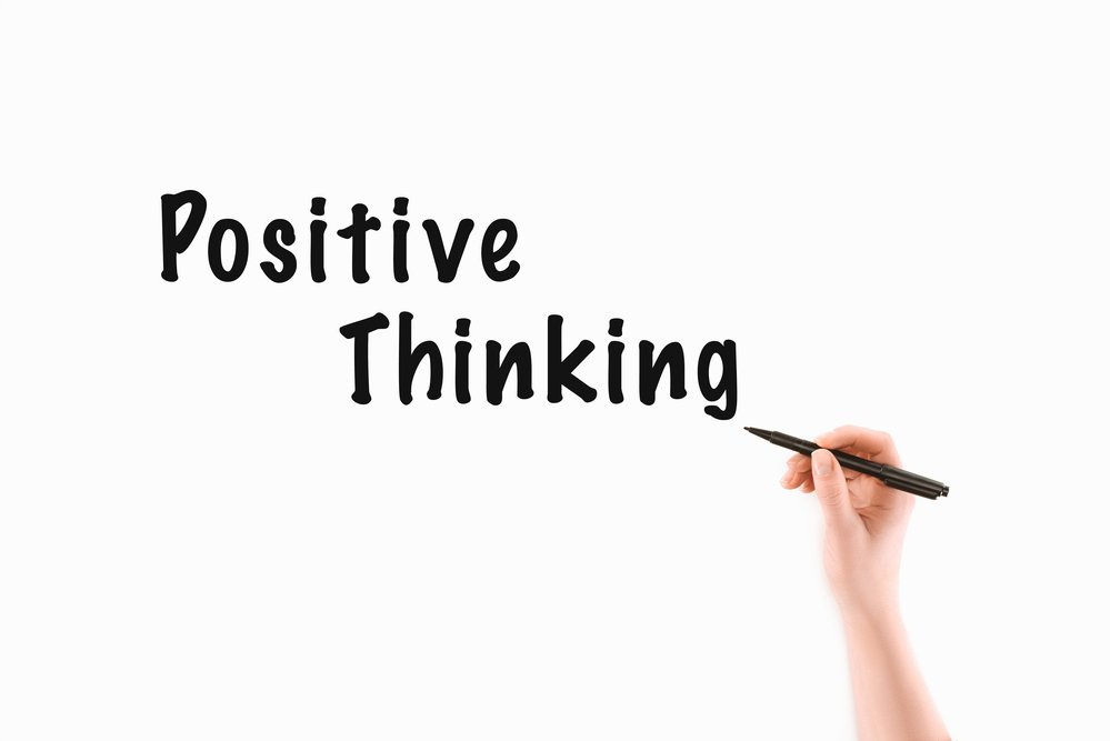 Positive Thinking written in black on a white board and a woman's hand holding a pen. Overcoming negative thoughts.