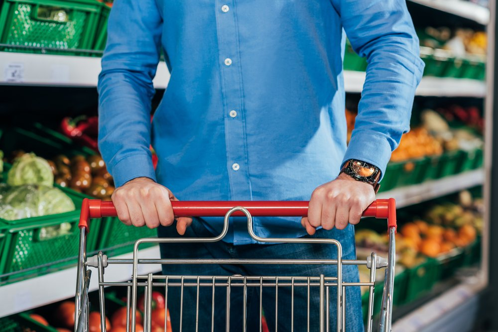 Cropped shot of a man with a shopping trolley in a supermarket. He is buying his shopping trolley essentials.