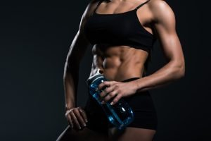 Muscular slim woman displaying her trim abs and midriff. What is the best workout for fat loss?