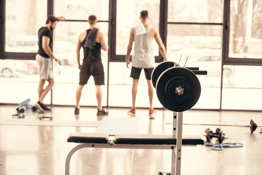 rear view of 3 men in a gym with gym equipment. A personal training course needs a hands on element.