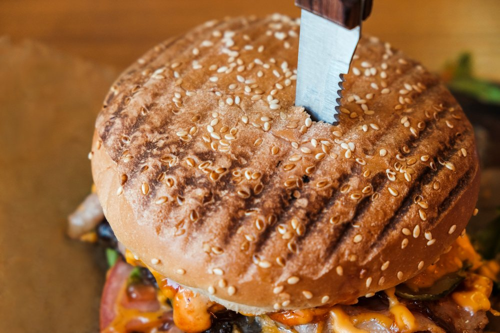 A close up of a hamburger with a knife in it. Achieving weight loss goals can mean being brutally honest about what you eat.