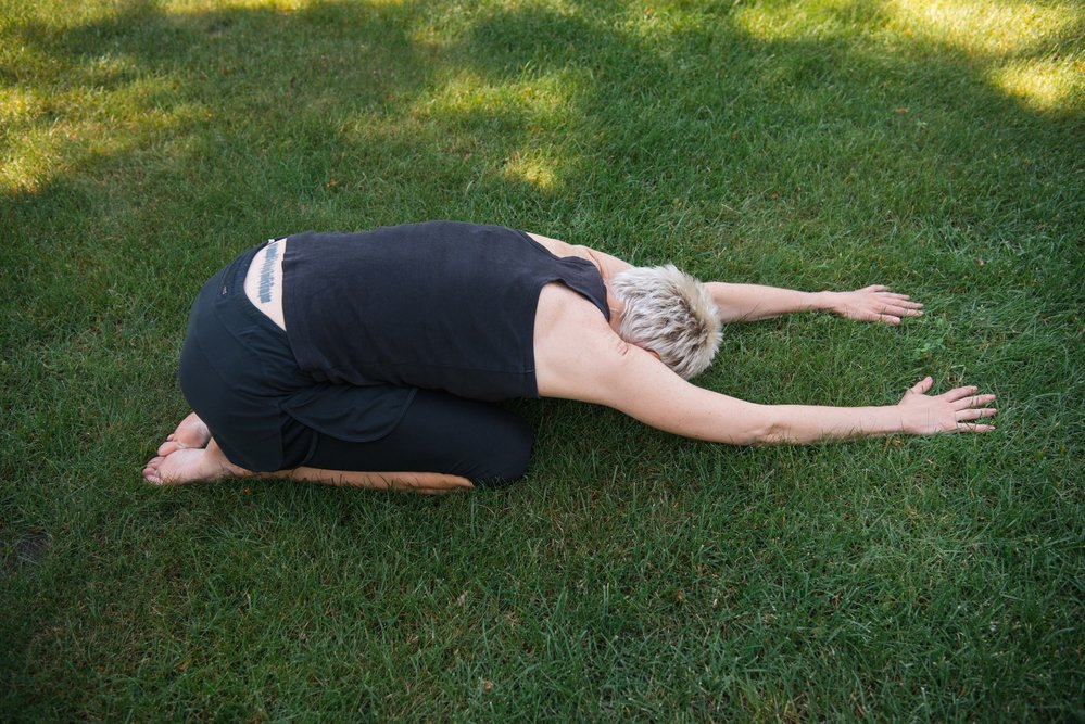 woman practising yoga (extended child pose) outside on the grass
