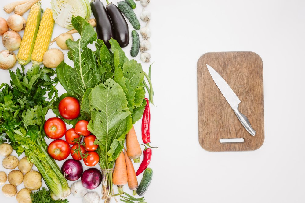 A 2-part picture with a selection of vegetables on the left and a wooden chopping board and knife on the right. Diet and body composition are linked.