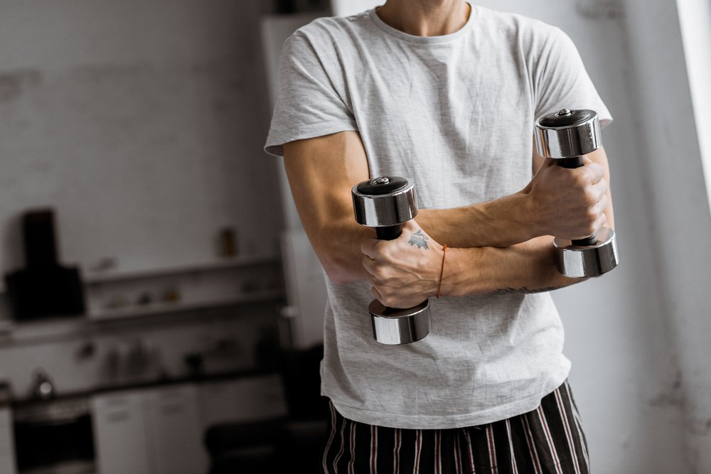 Cropped shot of a man in pyjamas holding dumbbells in his kitchen. Getting your exercise groove back can be hard.