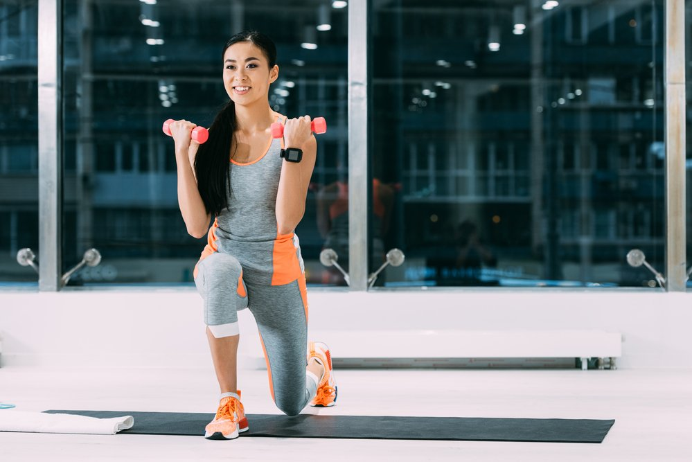 A young woman exercising with weights in a gym. Getting your exercise groove back can be hard.