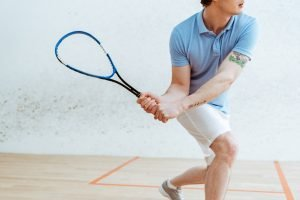 Cropped shot of a squash player in a pale blue top taking a shot using his squash equipment.