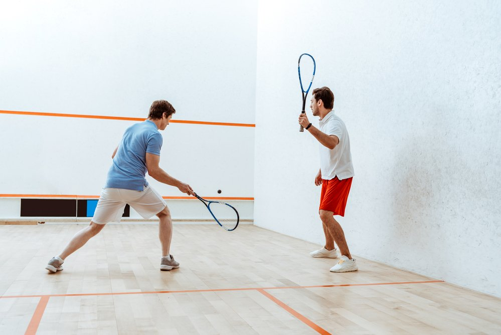 2 men on a squash court, playing squash, having learn how to play squash