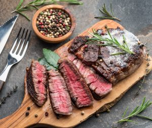 Medium rare Ribeye steak with herbs and a piece of butter on the wooden tray. Red meat is an excellent source of iron.