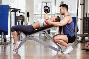 Personal trainer helping woman working with dumbbells. Each personal training course varies greatly.