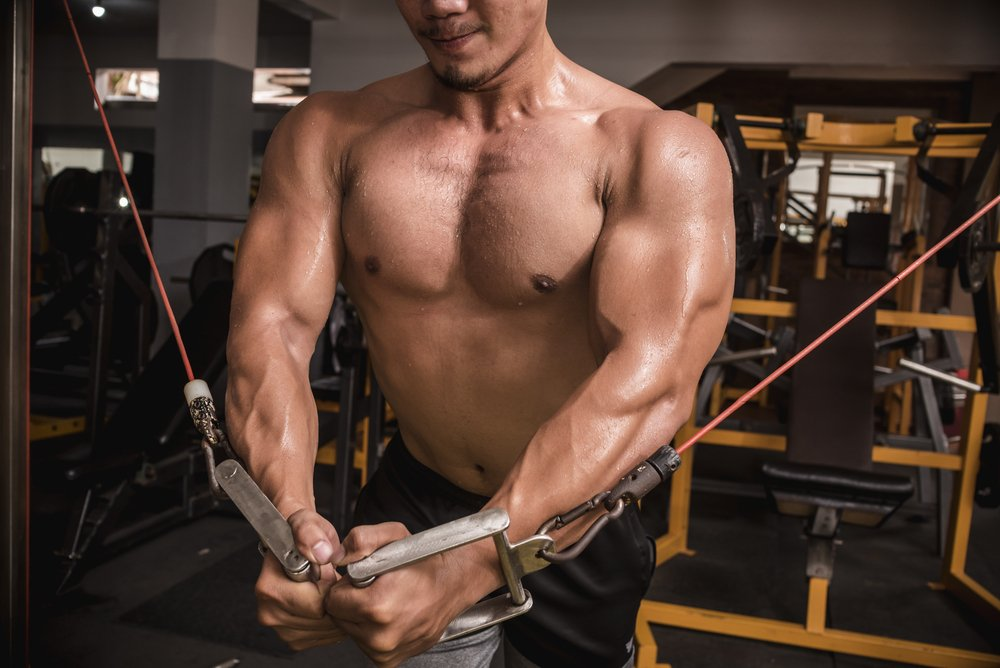 A muscular man doing cable crossovers at the gym. He is continuing to do weight training through injury