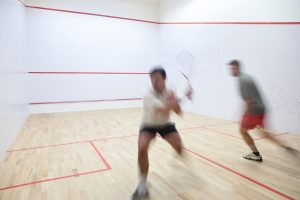 Squash players in action on a squash court (motion blurred image; color toned image). Learning how to play squash is not hard.