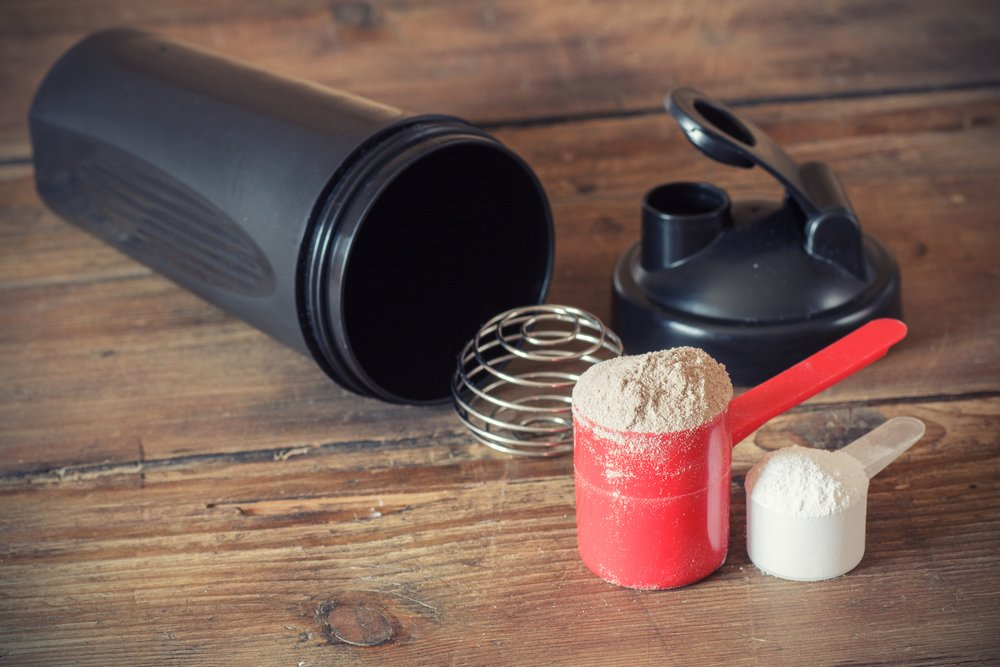 Whey protein powder in scoop and plastic shaker on wooden background. Cleaning your new protein shaker can be difficult.