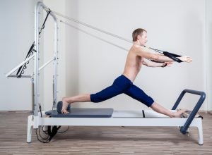 Pilates reformer workout exercises man at gym indoor. Pilates for men has many benefits.