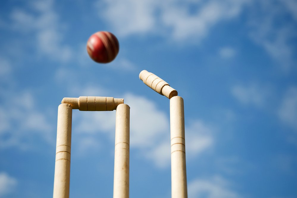 Cricket stumps and bails being hit by a ball against a background of a hot summer sky. An extreme heat policy is important for cricket.
