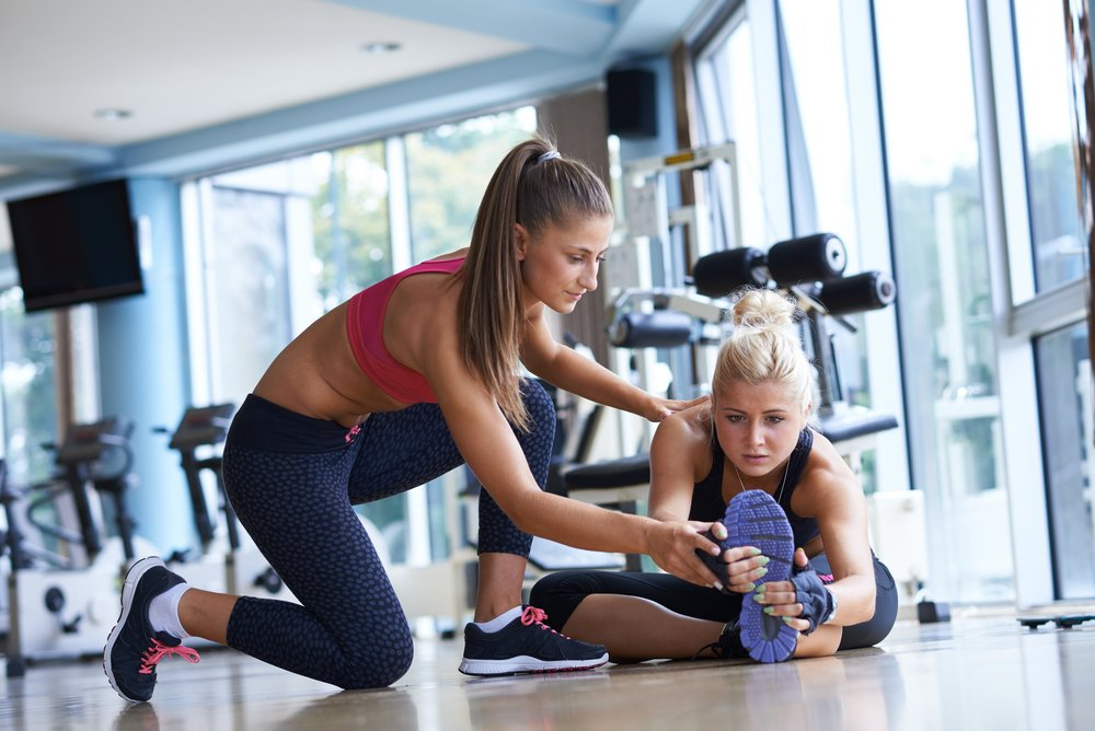 A woman working out in a gym with a female personal trainer. Tip for personal trainers can help with keeping clients.