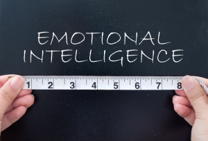 chalkboard writing of 'emotional intelligence' with a tape measure