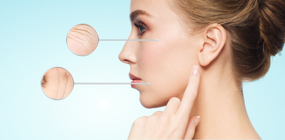 A young woman touching her face. Collagen stops the wrinkles forming in the focus bubbles.