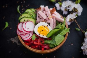 Why use a nutritionist? A healthy plate of Salad with ham, cucumber, spinach, Bulgarian pepper. Black background. Top view. Close-up