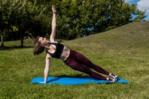 A young woman doing a side plank in the park. Core vs functional training